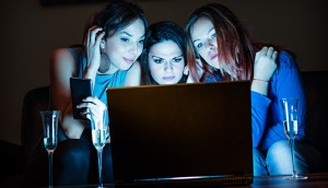 Three girlfriends, drinking champagne, watchng something interes