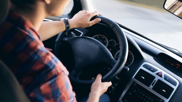 Young driver in his shirt in a nice modern car in motion