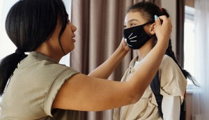 mother-putting-a-face-mask-on-her-daughter-4261252