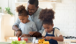 Happy biracial family involved in cooking tasty vegetarian dishes.